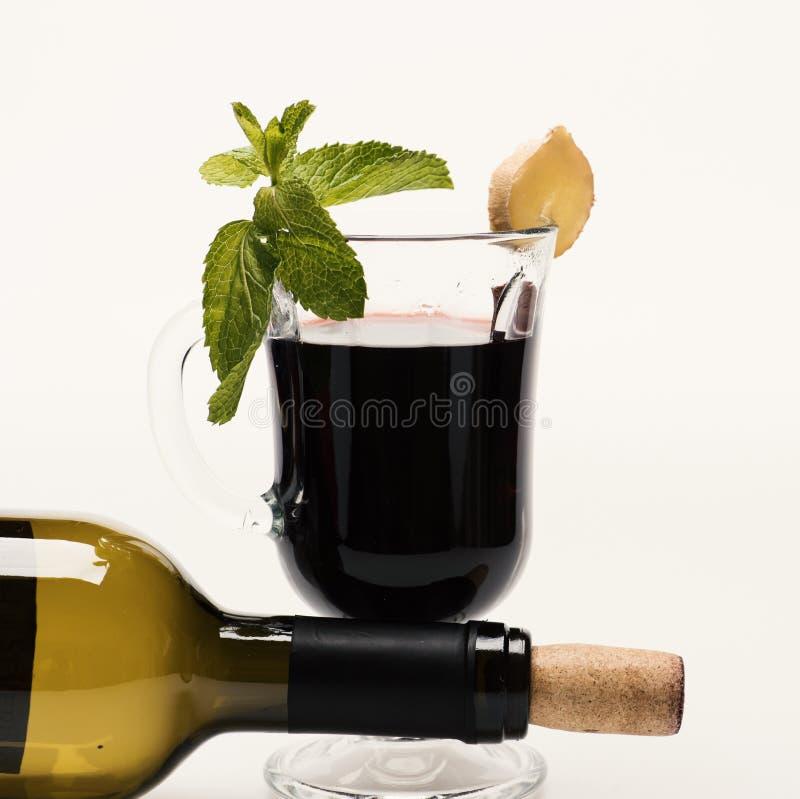 Θερμαμένο κρασί στο γυαλί με το συνδεμένο μπουκάλι ντεκόρ πλησίον στοκ φωτογραφία με δικαίωμα ελεύθερης χρήσης