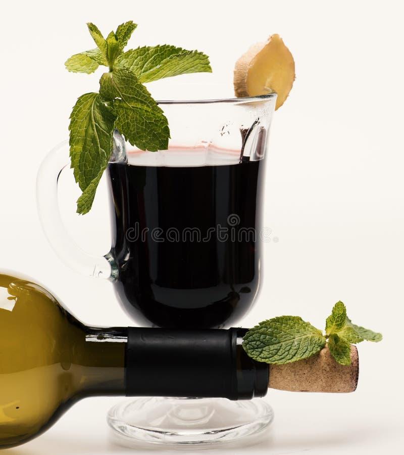 Θερμαμένο κρασί στο γυαλί με το συνδεμένο μπουκάλι ντεκόρ πλησίον στοκ εικόνες