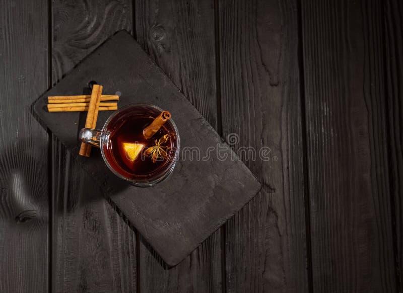 Θερμαμένο κρασί στο μαύρο ξύλινο πίνακα, τα ραβδιά κανέλας και την πορτοκαλιά, τοπ άποψη στοκ φωτογραφία με δικαίωμα ελεύθερης χρήσης