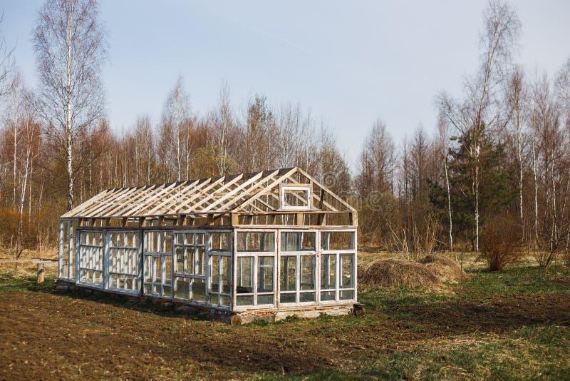 Θερμοκήπιο από τα παράθυρα στον κήπο την πρώιμη άνοιξη στοκ εικόνα με δικαίωμα ελεύθερης χρήσης