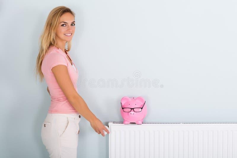 Θερμοστάτης ρύθμισης γυναικών με την τράπεζα Piggy στο θερμαντικό σώμα στοκ εικόνα με δικαίωμα ελεύθερης χρήσης