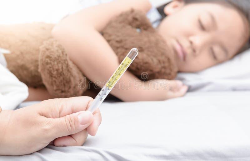 Θερμόμετρο εκμετάλλευσης χεριών μητέρων και άρρωστο κορίτσι που βάζουν στο κρεβάτι στοκ εικόνες με δικαίωμα ελεύθερης χρήσης