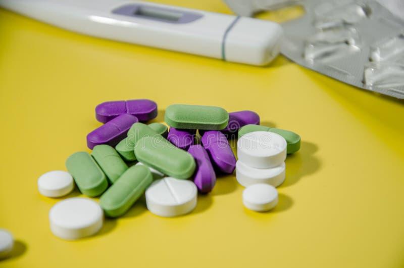 Θερμόμετρο και ένα σωρό διαφορετικά χάπια για όλες τις ασθένειες, κοντινό σε ένα φωτεινό κίτρινο φόντο στοκ φωτογραφίες