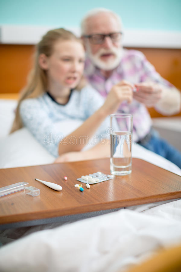 Θερμόμετρο με τα χάπια και το ποτήρι του νερού στοκ φωτογραφία με δικαίωμα ελεύθερης χρήσης
