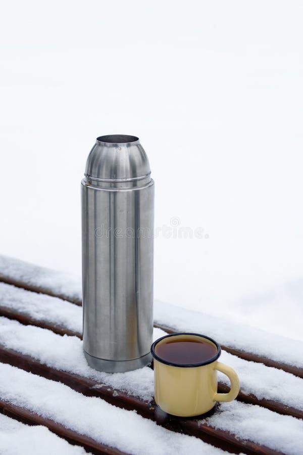 Θερμός και μεταλλικό κύπελλο με ζεστό τσάι σε ένα παγκάκι καλυμμένο με χιόνι σε ένα χειμερινό πάρκο στοκ εικόνες
