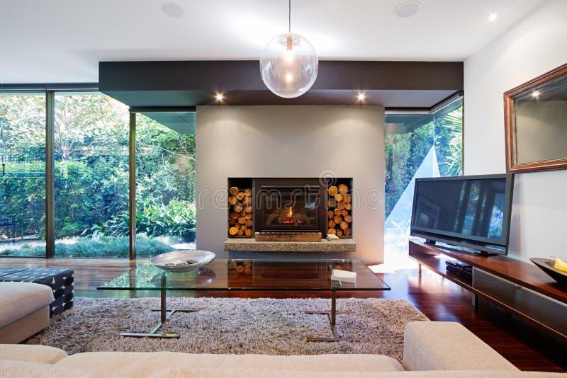 Θερμό αυστραλιανό καθιστικό με την εστία στο σπίτι πολυτέλειας στοκ εικόνα