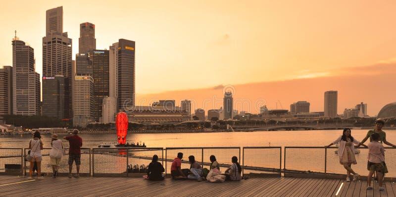 Θερμό ζωηρόχρωμο ηλιοβασίλεμα στα σύγχρονες κτήρια και τις αρχιτεκτονικές στις άμμους κόλπων μαρινών με τους ανθρώπους που χαλαρώ στοκ φωτογραφία με δικαίωμα ελεύθερης χρήσης
