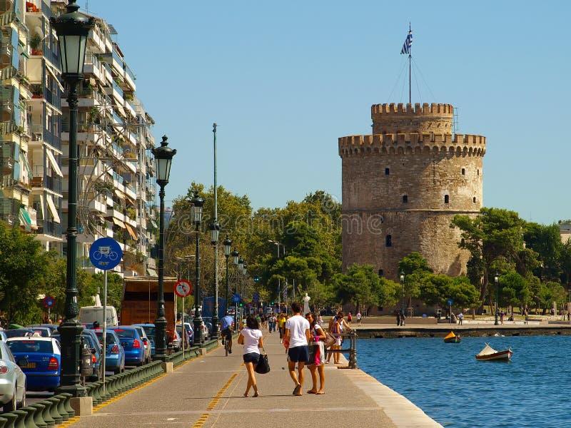 Θεσσαλονίκη, Ελλάδα - ο άσπρος πύργος στην ακτή του Αιγαίου πελάγους και του τουρίστα που περπατούν στον περίπατο στοκ φωτογραφία με δικαίωμα ελεύθερης χρήσης