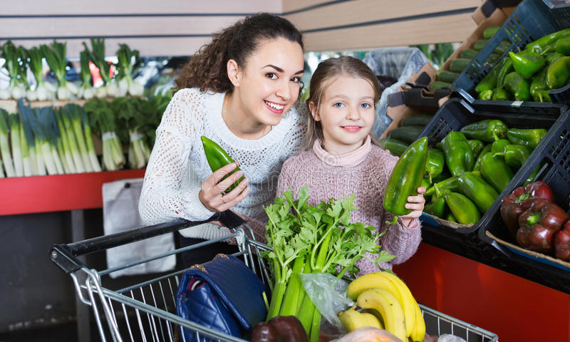 Θετικά θηλυκά και εύθυμα πράσινα veggies αγορών μικρών κοριτσιών στοκ φωτογραφία