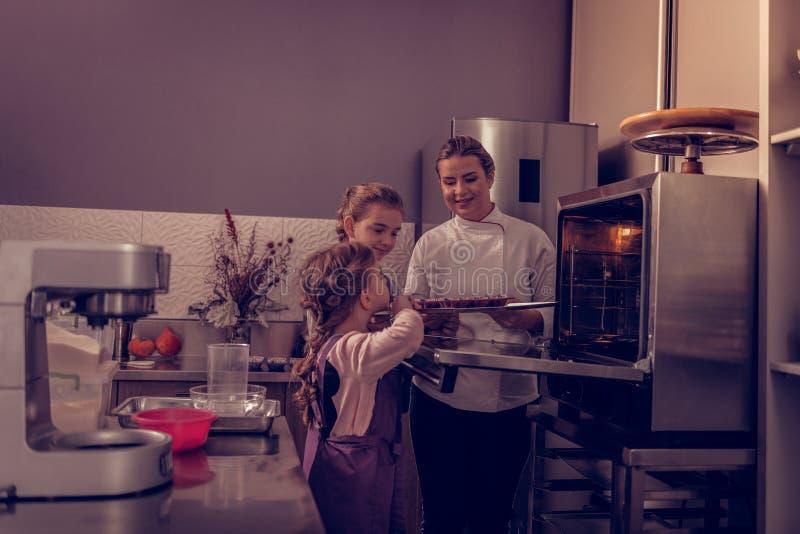 Θετικά όμορφα κορίτσια που βοηθούν τη μητέρα τους στην κουζίνα στοκ φωτογραφία