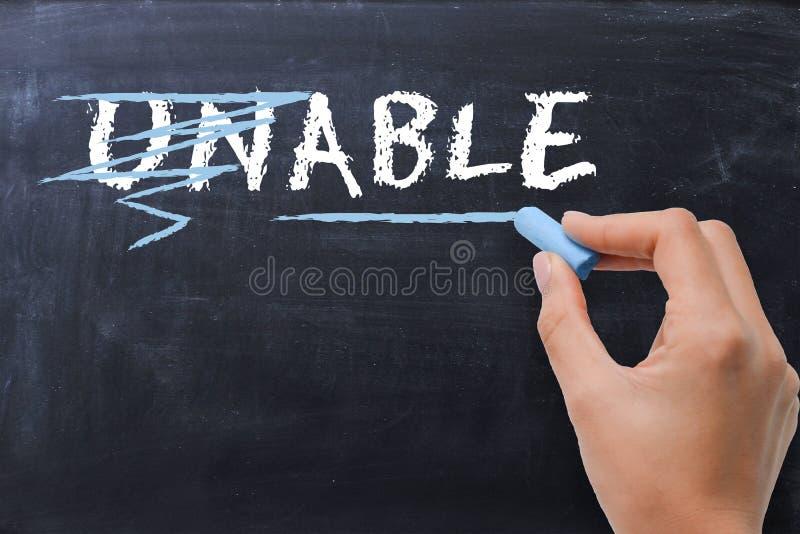 """Θετική έννοια σκέψης με τη γυναίκα που μετασχηματίζει τη λέξη """"unable† στη λέξη """"able† στον πίνακα κιμωλίας στοκ εικόνες"""