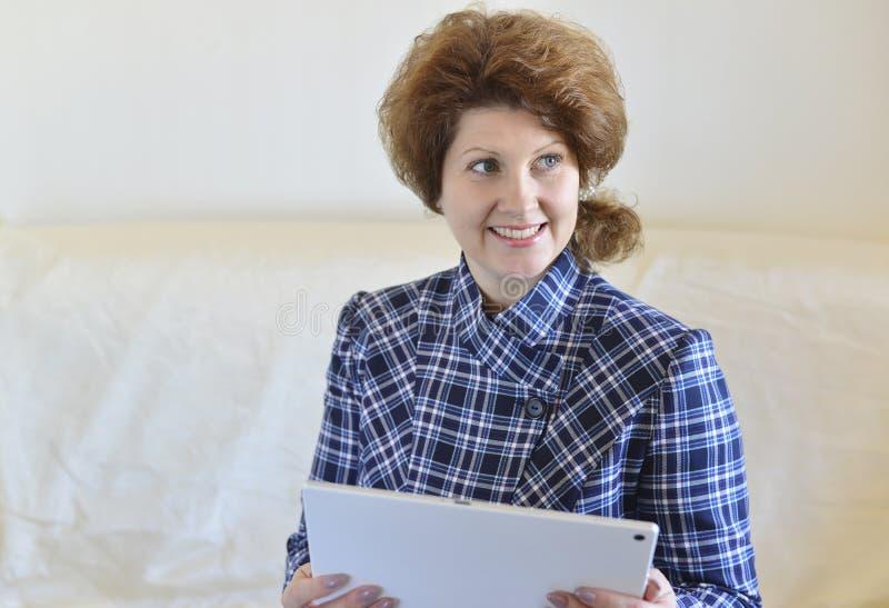 θετική γυναίκα με μια συνεδρίαση PC ταμπλετών στον καναπέ στοκ φωτογραφία