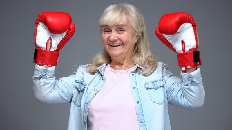 Θετική γυναίκα συνταξιούχων στα χέρια αύξησης εγκιβωτίζοντας γαντιών επάνω, έννοια επιτυχίας, πεποίθηση στοκ εικόνες με δικαίωμα ελεύθερης χρήσης
