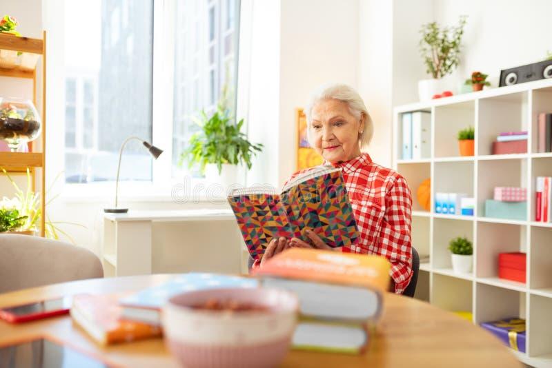 Θετική γυναίκα της Νίκαιας που διαβάζει ένα ενδιαφέρον βιβλίο στοκ εικόνες