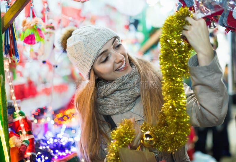 Θετική εύθυμη γυναίκα στην έκθεση κοντά στο μετρητή με το δώρο Χριστουγέννων στοκ φωτογραφίες με δικαίωμα ελεύθερης χρήσης