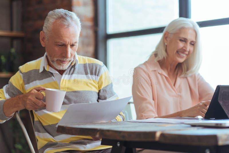 Θετική ηλικίας συνεδρίαση ατόμων στον πίνακα με τη σύζυγό του στοκ εικόνες