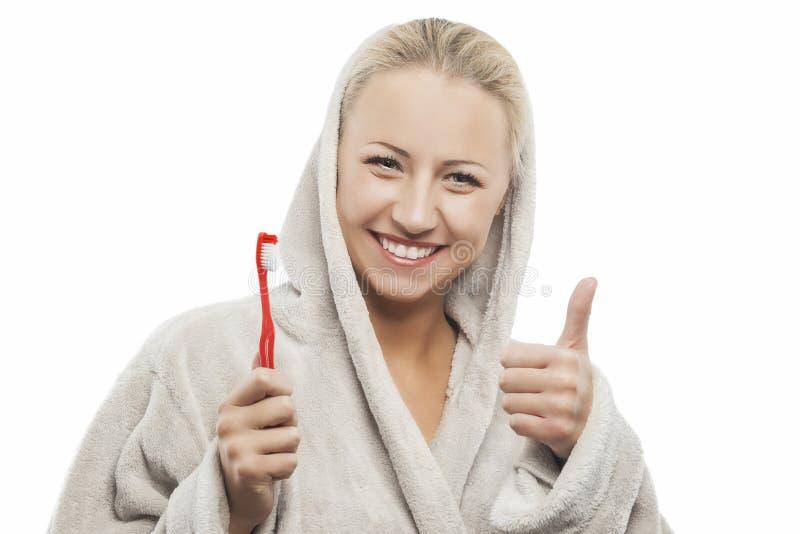 Θετική νέα ξανθή γυναίκα με τη χειρωνακτική οδοντόβουρτσα που παρουσιάζει αντίχειρες στοκ εικόνες με δικαίωμα ελεύθερης χρήσης