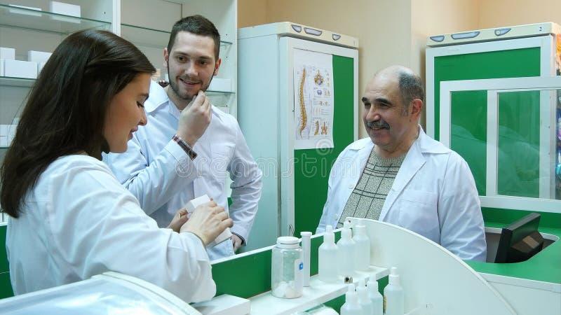 Θετική ομάδα του φαρμακοποιού που μιλά και που χαμογελά στο φαρμακείο νοσοκομείων στοκ φωτογραφία με δικαίωμα ελεύθερης χρήσης
