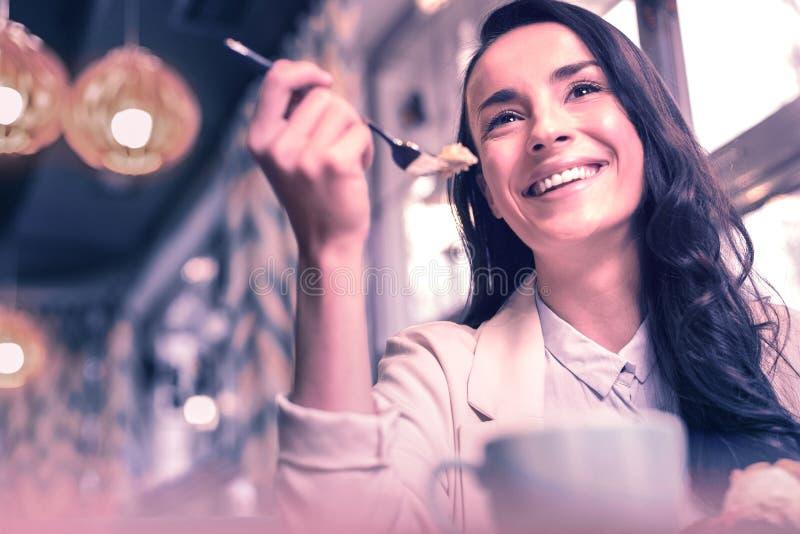 Θετική χαρούμενη συμπαθητική γυναίκα που τρώει το κέικ της στοκ εικόνες με δικαίωμα ελεύθερης χρήσης
