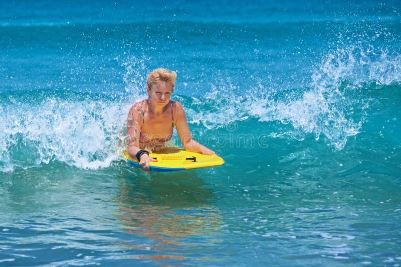 Θετική ώριμη γυναίκα που κάνει σερφ με τη διασκέδαση στα ωκεάνια κύματα στοκ φωτογραφία