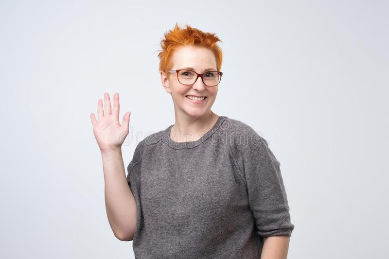 Θετική ώριμη καυκάσια γυναίκα με το κόκκινο hairstyle και γυαλιά που χαμογελούν το φιλικό και κυματίζοντας χέρι στη κάμερα στοκ εικόνες