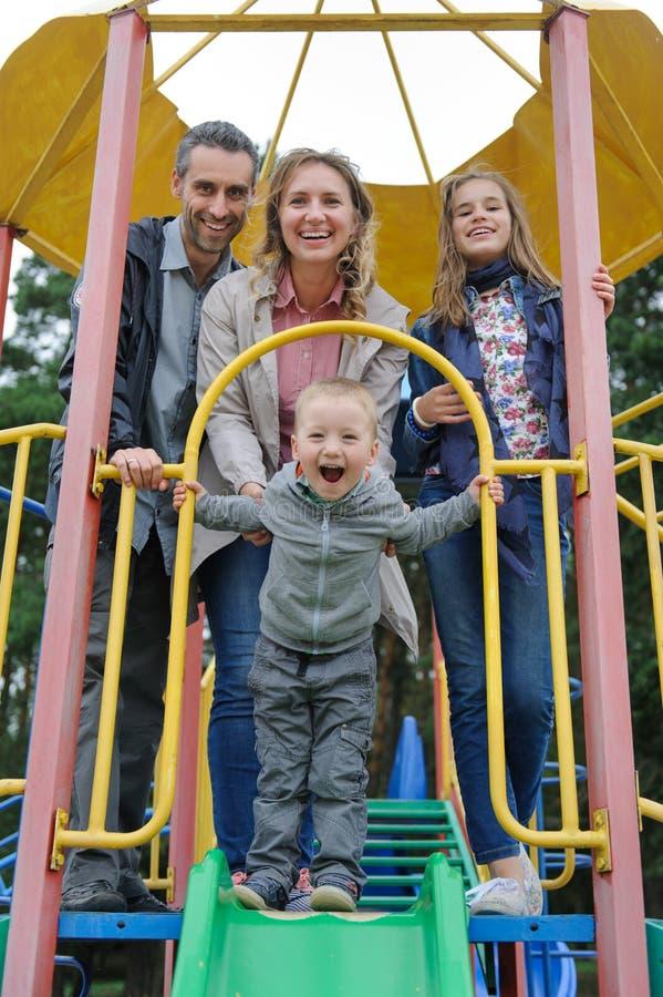 Θετικοί γονείς με το παιχνίδι γιων και κορών στη φωτογραφική διαφάνεια παιδιών ` s στοκ φωτογραφία με δικαίωμα ελεύθερης χρήσης