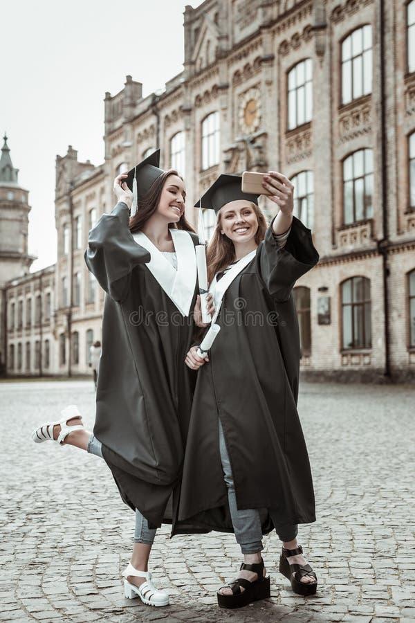 Θετικοί ευχαριστημένοι απόφοιτοι που κάνουν τις εικόνες στο smartphone στοκ φωτογραφία