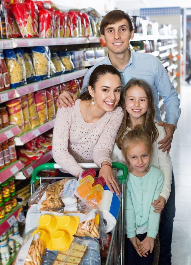 Θετικοί πελάτες με τα παιδιά που αγοράζουν τα τρόφιμα στην υπεραγορά στοκ εικόνα