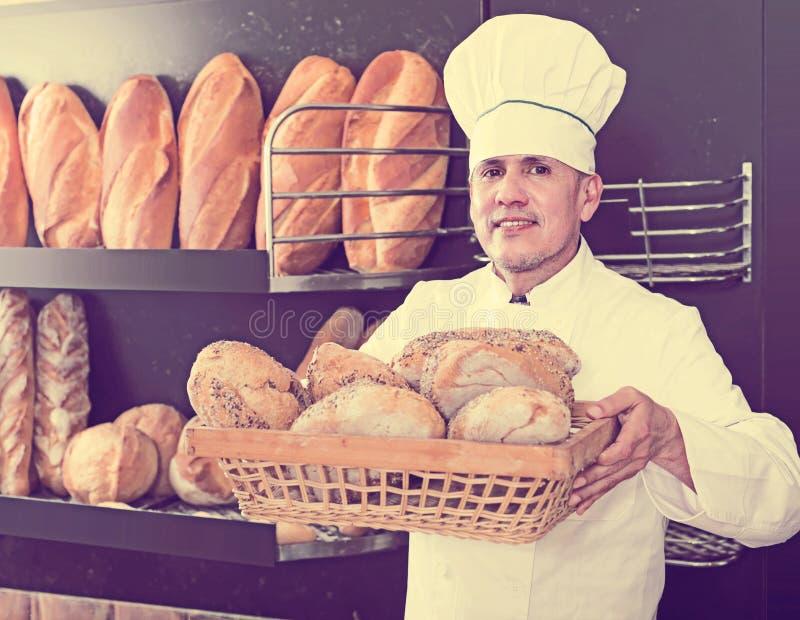 Θετικός άνδρας εργαζόμενος αρτοποιείων με τα νόστιμα και φρέσκα προϊόντα ψωμιού στοκ εικόνα