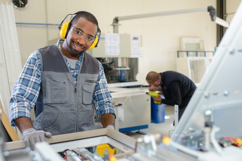 Θετικός χαμογελώντας εργαζόμενος στη μηχανή τόρνου στο εργοστάσιο στοκ εικόνα