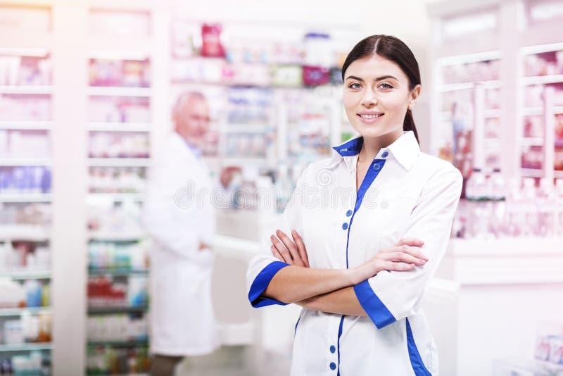 Θετικός druggist με τα διασχισμένα χέρια που περιμένει τους πελάτες στοκ εικόνα