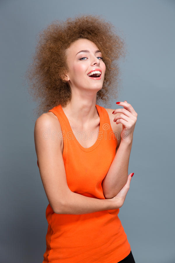 Download Θετικό γελώντας σγουρό κορίτσι στην πορτοκαλιά κορυφή στο γκρίζο υπόβαθρο Στοκ Εικόνα - εικόνα από κάνετε, closeup: 62723923