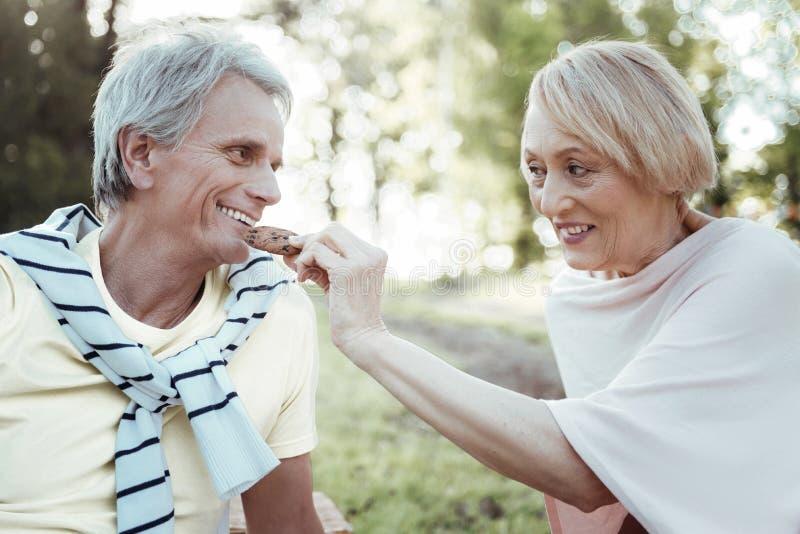 Θετικό ευχαριστημένο άτομο που πηγαίνει να φάει το νόστιμο μπισκότο στοκ εικόνες με δικαίωμα ελεύθερης χρήσης