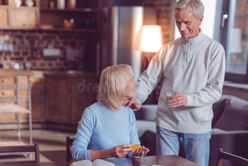 Θετικό ευχαριστημένο αρσενικό πρόσωπο που δίνει το νερό στη σύζυγό του στοκ εικόνες