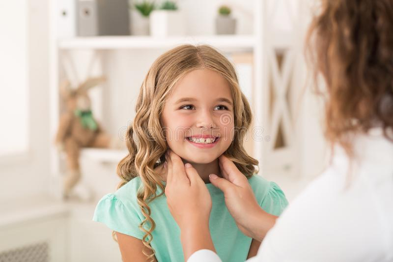 Θετικό κορίτσι που κοιτάζει επίμονα στο θηλυκό γιατρό που που ελέγχει τις αμυγδαλές της στοκ φωτογραφία