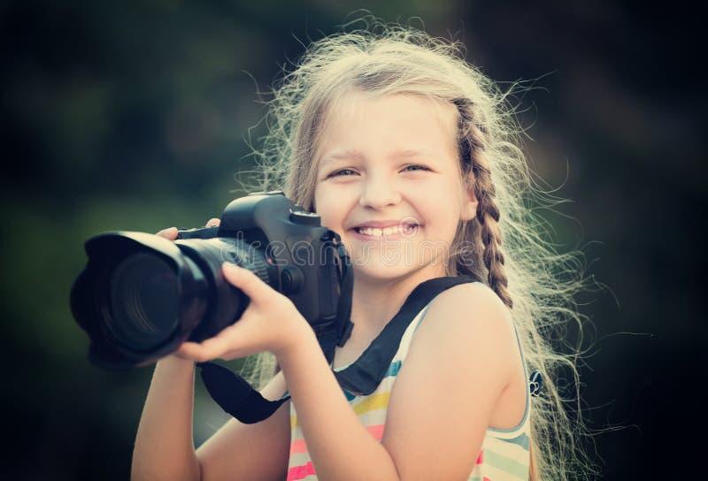 Θετικό κορίτσι που παίρνει τις εικόνες με τη κάμερα στο πάρκο στοκ εικόνα