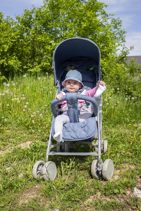 Θετικό μικρό κορίτσι σε έναν περιπατητή που παίζει με τα πόδια της σε έναν περίπατο Το ηλιόλουστο μωρό ημέρας κλωτσά τα πόδια στη στοκ εικόνα