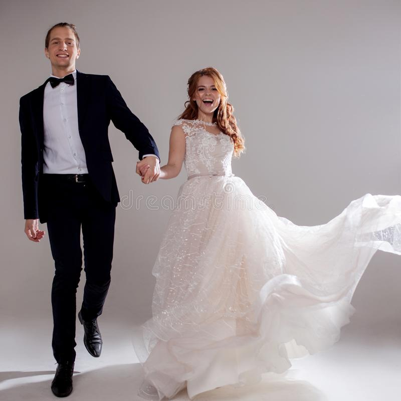 Θετικό νέο ζεύγος που γελά και που χορεύει από κοινού Το ζεύγος στο στούντιο ένα ελαφρύ υπόβαθρο στοκ φωτογραφία με δικαίωμα ελεύθερης χρήσης