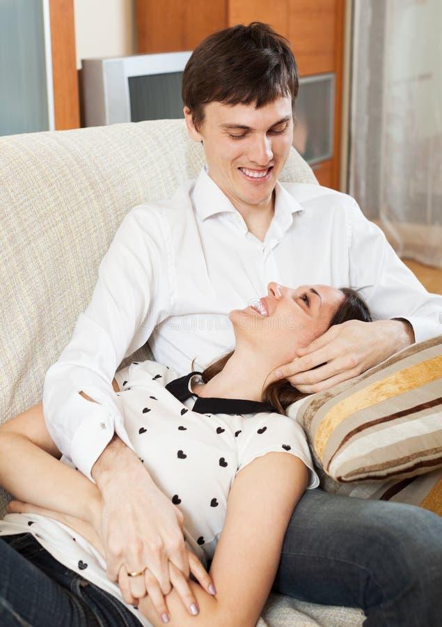 Θετικό νέο ζεύγος στον καναπέ στοκ φωτογραφίες με δικαίωμα ελεύθερης χρήσης