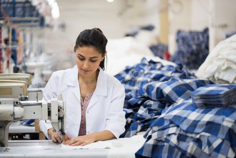 Θετικό νέο ράψιμο γυναικών με την επαγγελματική μηχανή στο εργαστήριο στοκ φωτογραφίες με δικαίωμα ελεύθερης χρήσης
