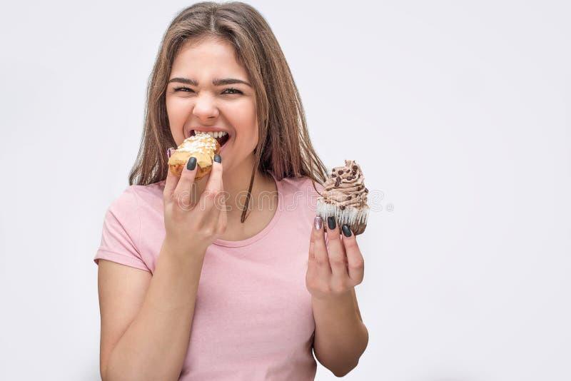 Θετικό νέο χαμόγελο γυναικών στη κάμερα Δαγκώνει το κομμάτι ECLAIR Πρότυπο κέικ λαβής σε ένα άλλο χέρι Απομονωμένος στο γκρι στοκ εικόνες