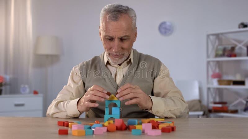 Θετικό παλαιό παιχνίδι ατόμων με τους ξύλινους κύβους, γνωστική κατάρτιση στο Alzheimer στοκ εικόνες με δικαίωμα ελεύθερης χρήσης