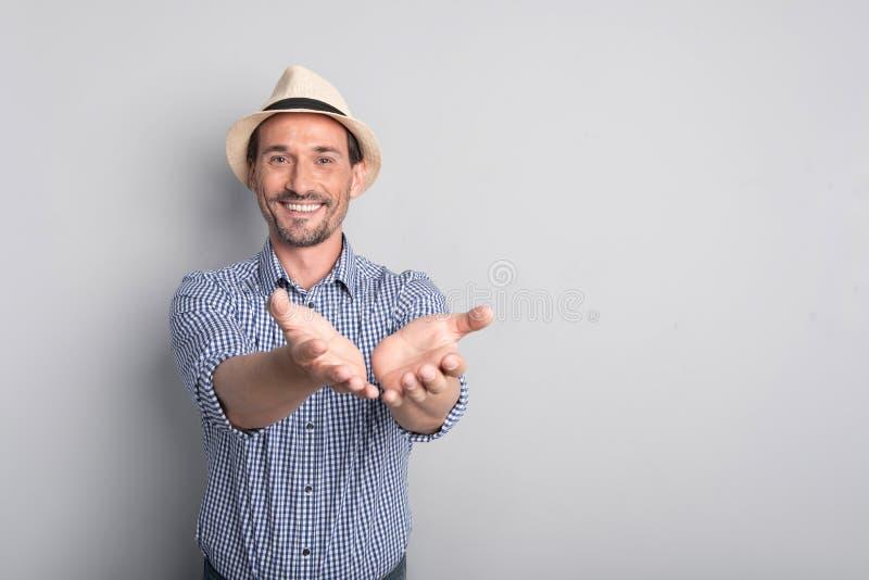 Θετικό χαρούμενο άτομο που προσποιείται να δώσει κάτι στοκ φωτογραφία