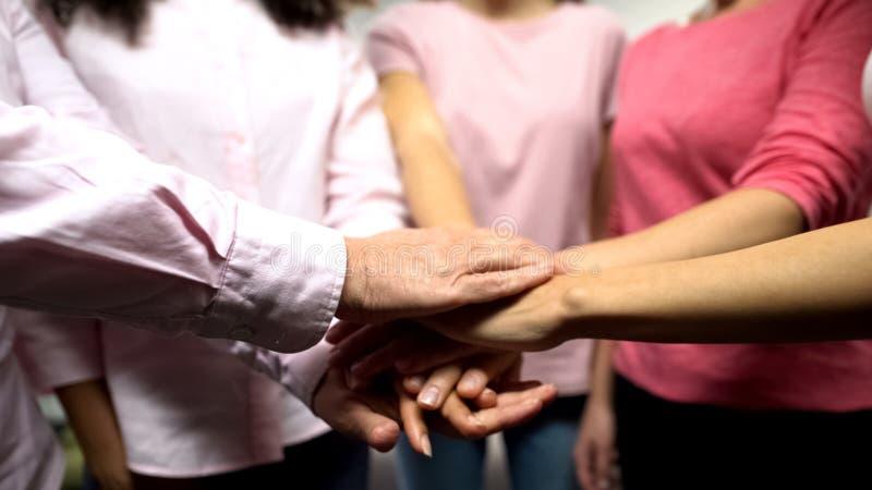 Θηλυκά με τον καρκίνο στα ρόδινα πουκάμισα που βάζουν τα χέρια μαζί, υπ στοκ εικόνα με δικαίωμα ελεύθερης χρήσης