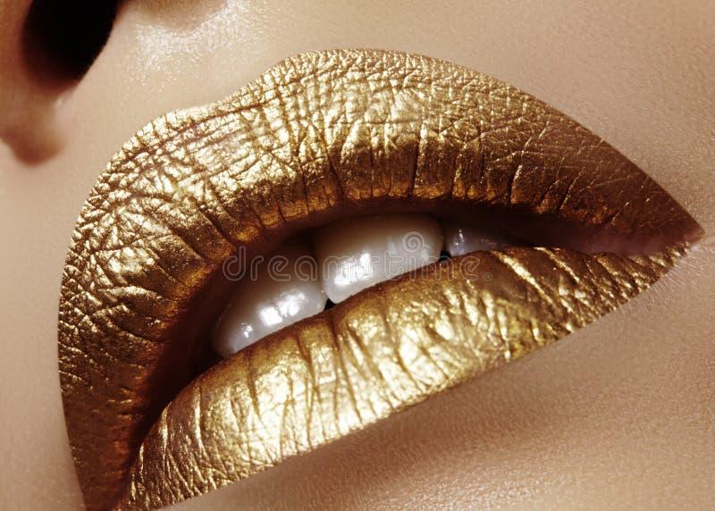 Θηλυκά παχουλά χείλια κινηματογραφήσεων σε πρώτο πλάνο με το χρυσό χρώμα Makeup Η μόδα γιορτάζει τη σύνθεση, ακτινοβολεί καλλυντι στοκ φωτογραφία με δικαίωμα ελεύθερης χρήσης