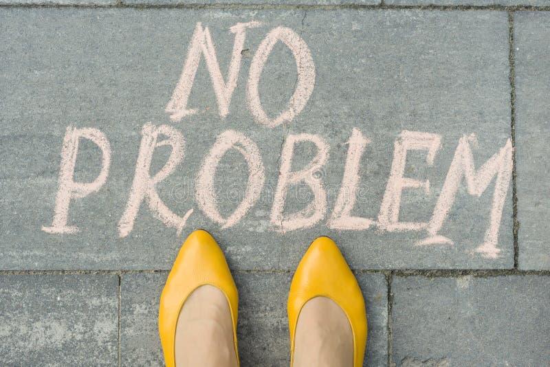 Θηλυκά πόδια με το κείμενο κανένα πρόβλημα που γράφεται στο γκρίζο πεζοδρόμιο στοκ φωτογραφίες με δικαίωμα ελεύθερης χρήσης