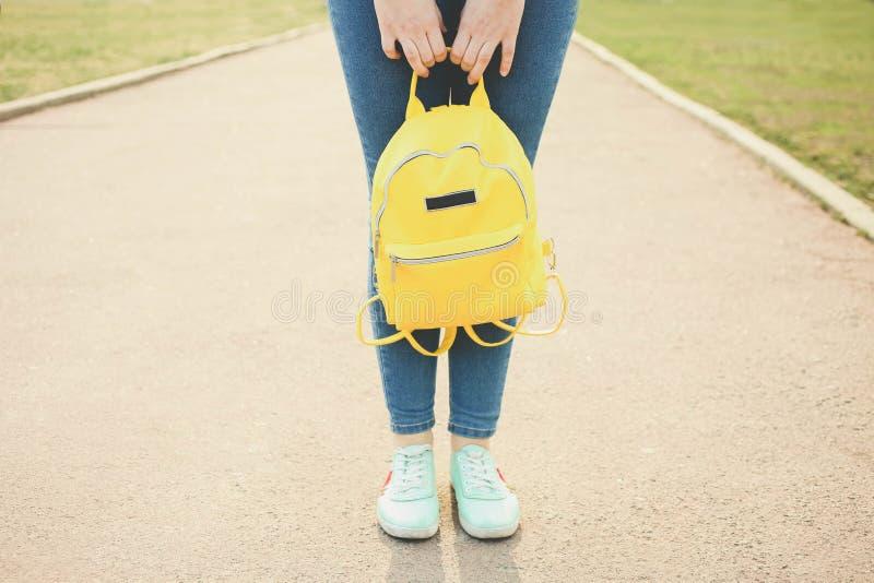 Θηλυκά πόδια με το φωτεινό μοντέρνο κίτρινο σακίδιο πλάτης στοκ φωτογραφίες