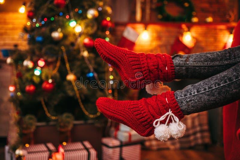 Θηλυκά πόδια προσώπων στις εύθυμες κόκκινες κάλτσες, Χριστούγεννα στοκ εικόνα