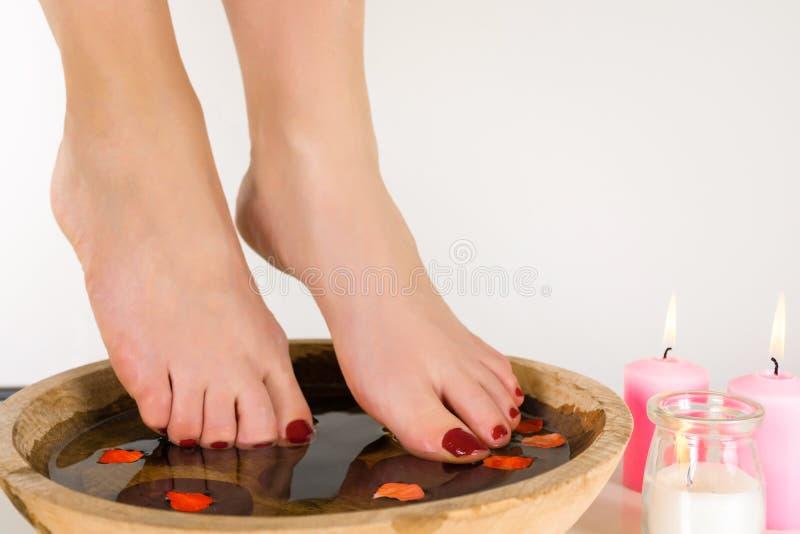 Θηλυκά πόδια σε ένα ξύλινο κύπελλο με το νερό και τα ρόδινα κεριά που καίνε στο πάτωμα στοκ φωτογραφίες