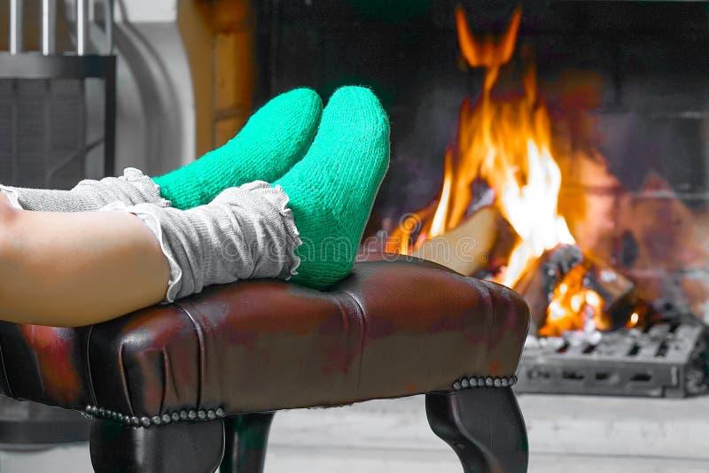 Θηλυκά πόδια στις κάλτσες κοντά στην εστία στοκ φωτογραφία